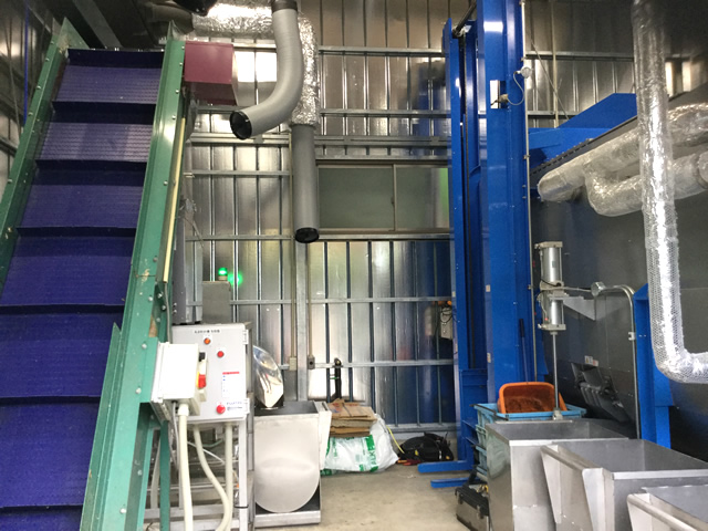 左側が投入コンベア。コンベアの裏に食品リサイクル粉砕機、その下に脱水機。向かい側に青色の反転投入機と銀色の熱風乾燥機。